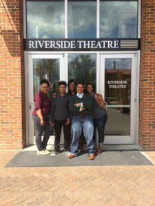 Five students standing and posing in front of the doors of a theater all smiling with the sun shining on them from the left side