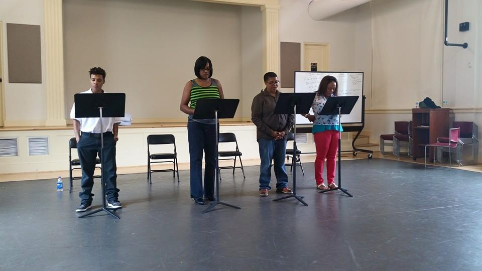 Four actors standing in front of music stands rehearsing their lines with a stage in the background