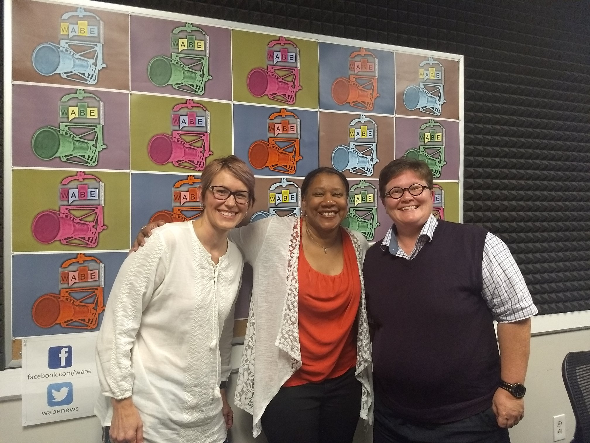 Three people standing together and smiling at the camera at local radio station