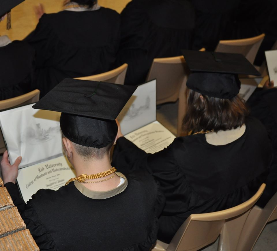 Two graduates wearing mortarboard and gowns looking down at their diploma