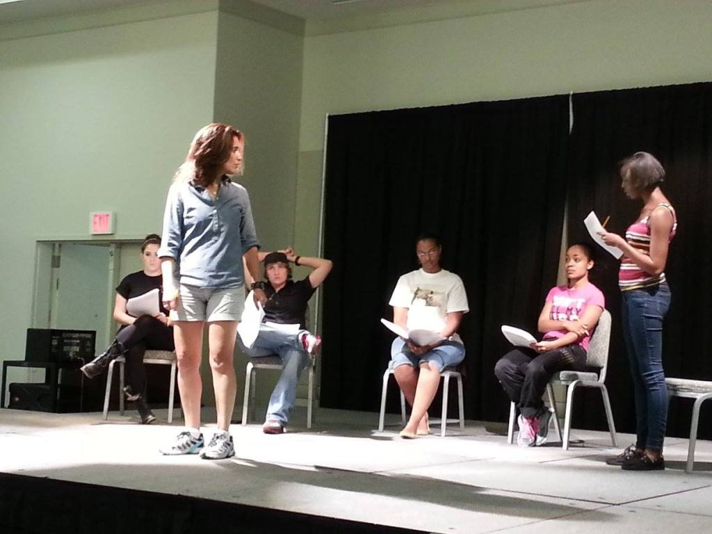 Two people rehearsing and making changes while others sit and observe behind them